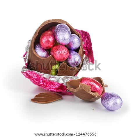Broken chocolate Easter egg wrapped in pink foil with candies on white background - stock photo
