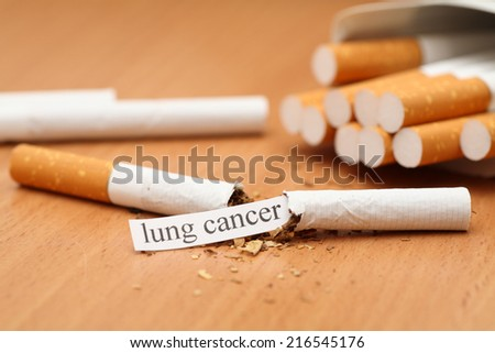 """Broken cigarette with message """"Lung Cancer"""". Shallow depth of field. Close-up. - stock photo"""