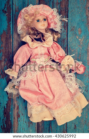 Broken doll on a wooden background. - stock photo