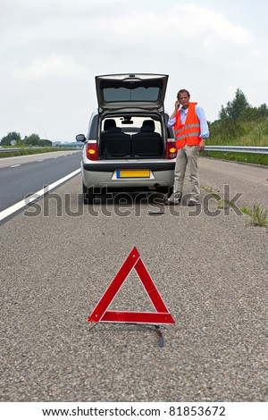 Broken down car at the side of the road, with a man, wearing a reflective vest calling for assistance, a warning triangle. proper procedure of road safety - stock photo