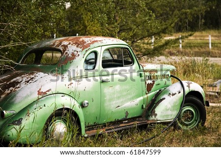 Broken down vintage car on the side of the road. - stock photo