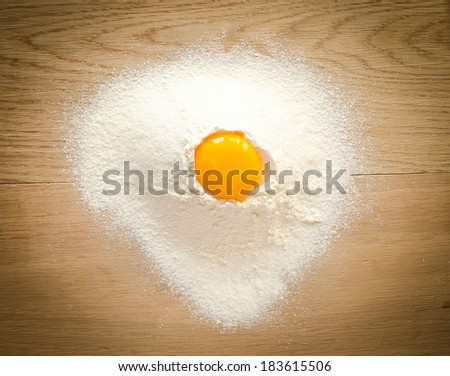 Broken egg in flour - stock photo