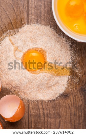 Broken egg lying in the heap of flour near the eggs shells and white plate with yolks inside on the wooden table. Top view - stock photo