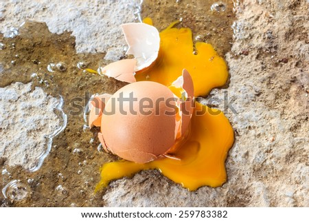 broken egg on dirty ground - stock photo