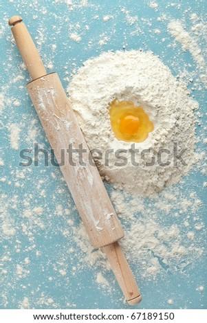 Broken egg on flour, means for making bread - stock photo