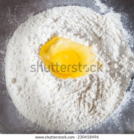 Broken egg on flour, means for making bread closeup - stock photo