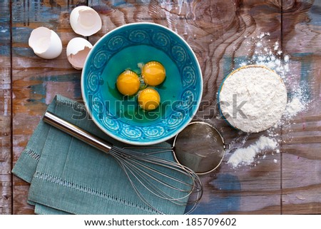 Broken eggs in a bowl, flour and various tools next to them on wooden table. Above view.  - stock photo