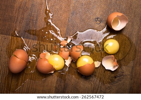 Broken eggs on the wooden floor. - stock photo