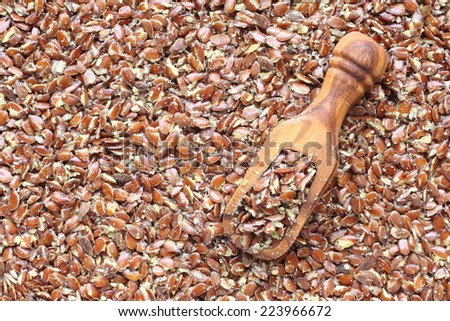 Broken flax seeds in wooden scoops (contain a lot of fibre) - stock photo