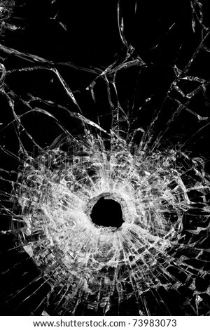 broken glass isolated on black - authentic bullet hole - close up - stock photo