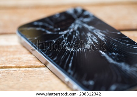 Broken glass of smart phone on the wood table. Selective focus. - stock photo