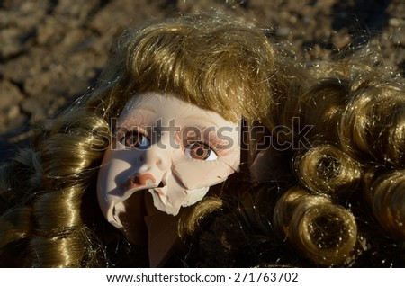 Broken head of porcelain doll lying on the ground - stock photo