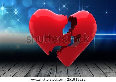 Broken heart against shimmering light design over boards - stock photo