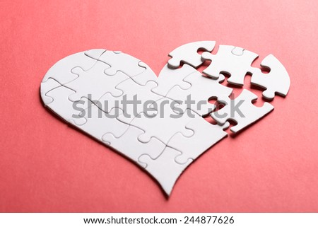 Broken Heart Made Of White Jigsaw Puzzle Over Orange Background - stock photo