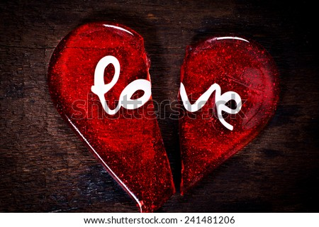 Broken heart with love sign on wooden background - stock photo