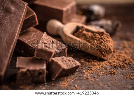 Broken homemade chocolate bar on wooden background - stock photo