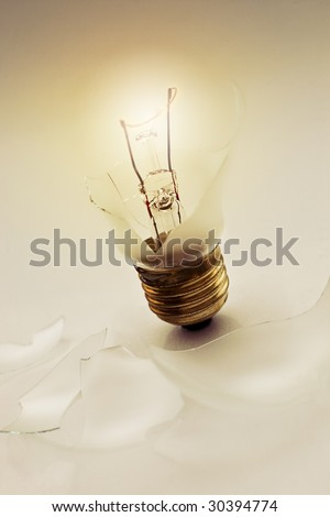 Broken light bulb still glowing. - stock photo