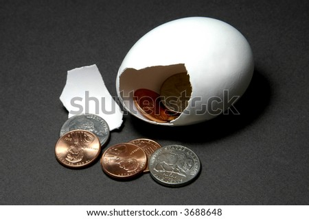 broken nestegg with US pennies and nickels - stock photo