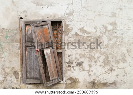 Broken old window on old cracked wall - stock photo