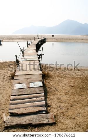 Broken old wooden bridge in beach - stock photo