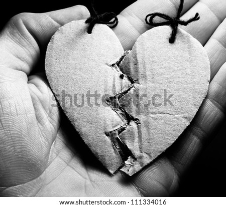 Broken paper heart on a hand. Black and white style - stock photo