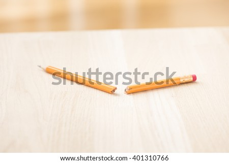 Broken pencil lying on table. Concept of frustration, writers block and school problem. - stock photo