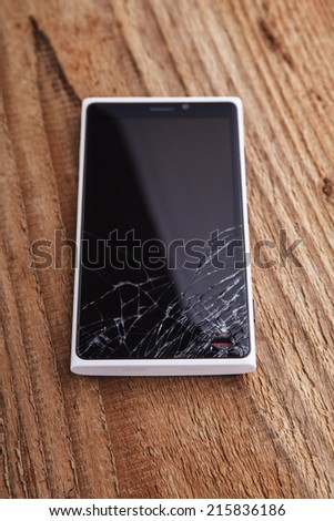 Broken phone on wooden background - stock photo