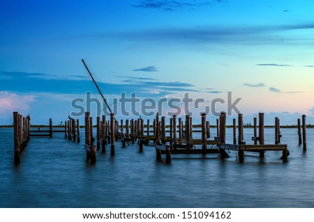 Broken pier and mast of broken ship in water after sunset in Biloxi, Mississippi - stock photo