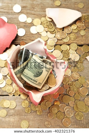 Broken piggy bank with cash and coins on wooden background