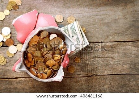 Broken piggy bank with cash and coins on wooden background - stock photo