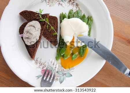 broken poached eggs on the green beans