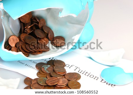 Broken Porcelain Piggy Bank spilling out Pennies atop Tuition Statement - stock photo