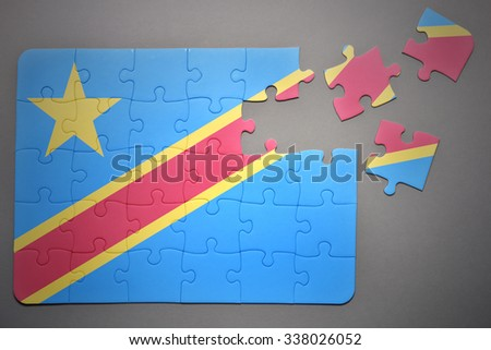 broken puzzle with the national flag of democratic republic of the congo on a gray background - stock photo