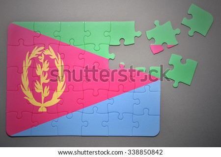 broken puzzle with the national flag of eritrea on a gray background - stock photo