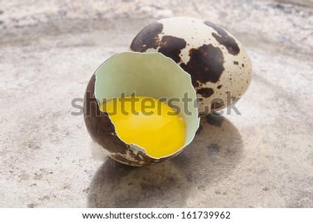 Broken quail egg on silver plate - stock photo