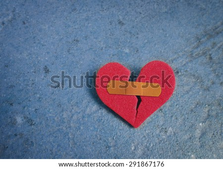 Broken red heart with a bandaid, on blue                                - stock photo
