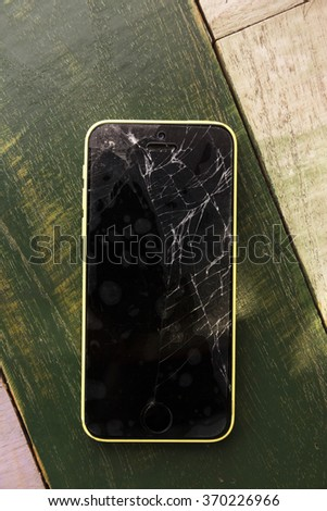 Broken screen mobile phone on wooden table