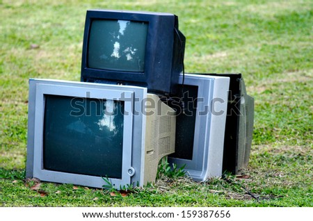 Broken television stacked for disposal outdoor. - stock photo