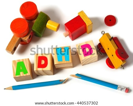 Broken toys and wooden blocks with letters ADHD - stock photo