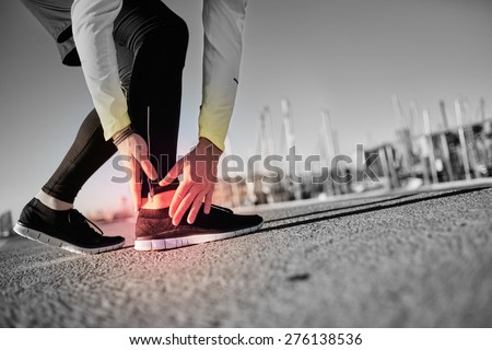 Broken twisted ankle - running sport injury. Athletic man runner touching foot in pain due to sprained ankle. - stock photo