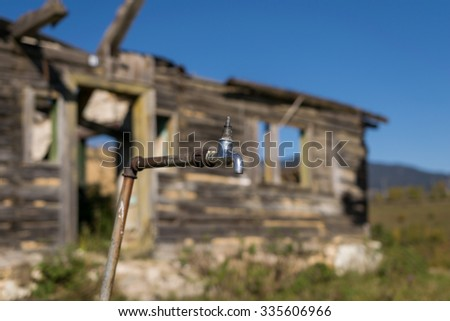 Broken water tap with abandoned building background - stock photo