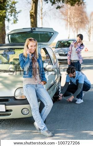 Broken wheel man changing tire help two female friends - stock photo