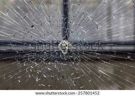 Broken window, cracked glass on urban background - stock photo