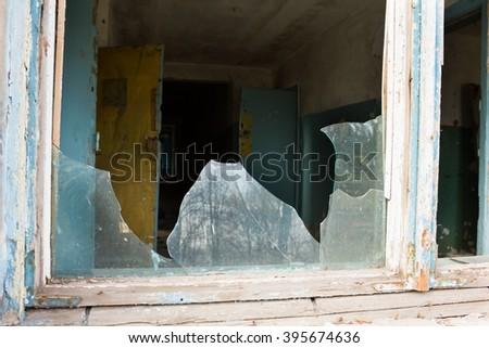 Broken window in an abandoned  building - stock photo