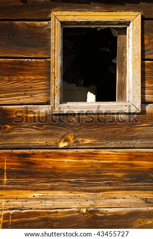 Broken window on an old, abandoned wooden house - stock photo