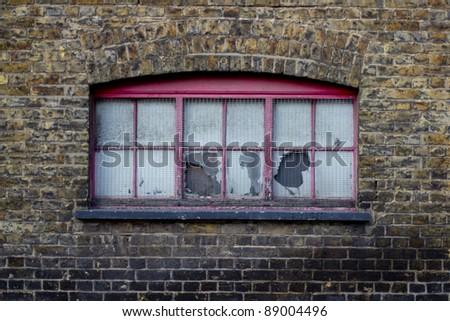 Broken window on old brick building - stock photo