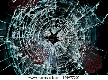 Broken window with a hole in the middle and finger prints                               - stock photo