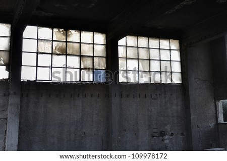 Broken windows and concrete wall in abandoned factory interior. - stock photo