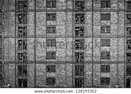 Broken windows in huge derelict warehouse. (Stanley Dock, Liverpool, UK, largest brick built warehouse in the world) - stock photo