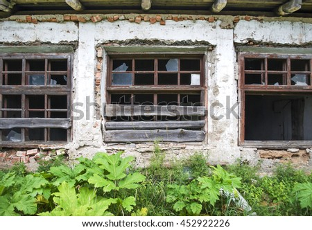 Broken windows of an abandoned building - stock photo